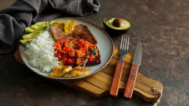 Beef steak with tomatoes sauce, rice, avocado, bananas fries Premium Photo