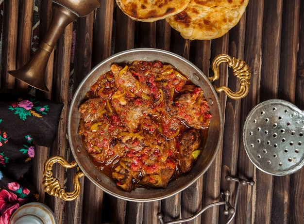 Beef stew in tomato sauce inside copper pan. Free Photo