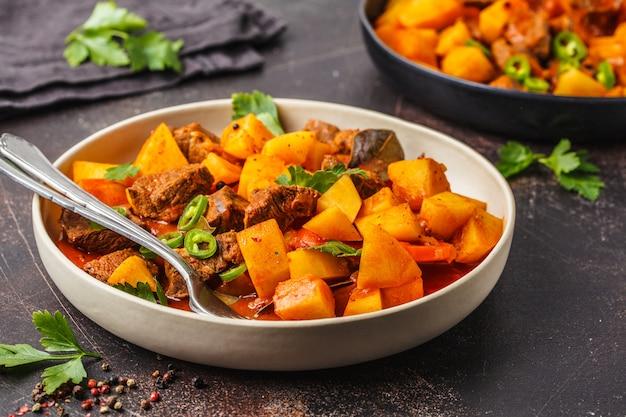 Beef stewed with potatoes in tomato sauce, dark background. Premium Photo