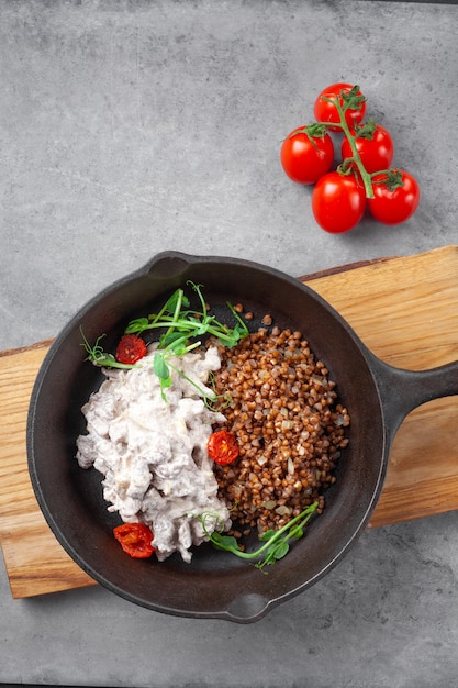 Бефстроганов в сливках с гречневой крупой и помидорами черри на сковороде Premium Фотографии