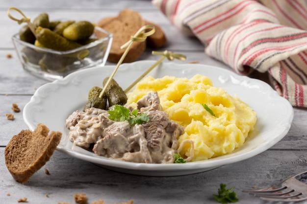 Бефстроганов с говядиной в сливочном соусе, картофельным пюре и солеными огурцами Premium Фотографии
