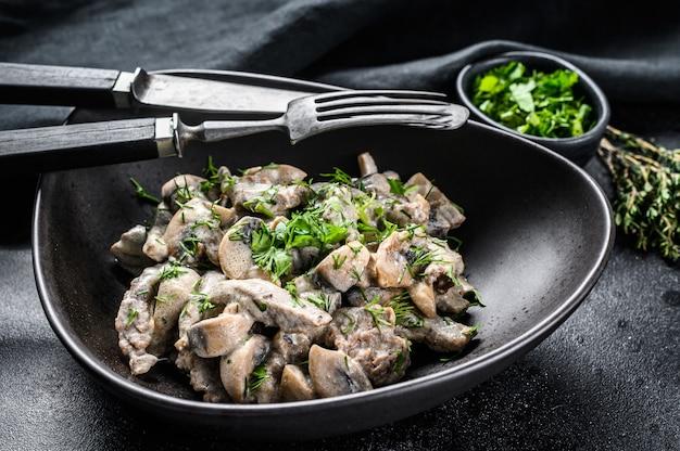Бефстроганов с грибами и свежей петрушкой в тарелку на черном столе. Premium Фотографии