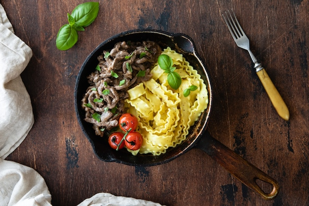 Бефстроганов с помидорами, базиликом и пастой. вид сверху Premium Фотографии