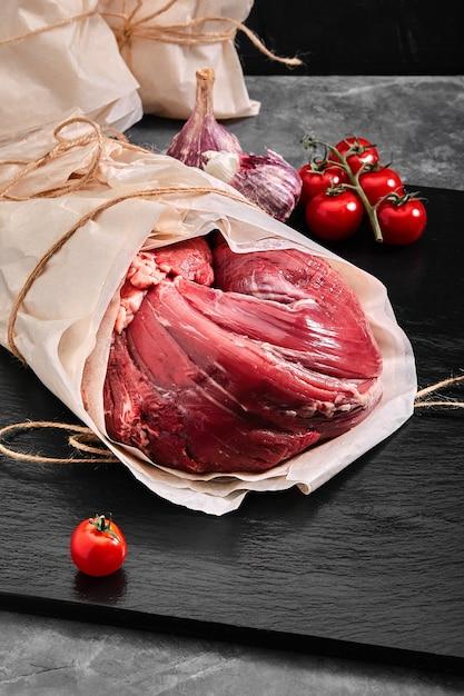 Говяжья вырезка из сырого мяса. доставка еды, серый фон. Premium Фотографии