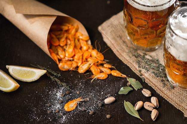 ビールと木製のテーブルでエビのグリル Premium写真