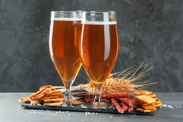 Beer and appetizing beer snacks set. table with mug of beer, wooden board with sausages Premium Photo