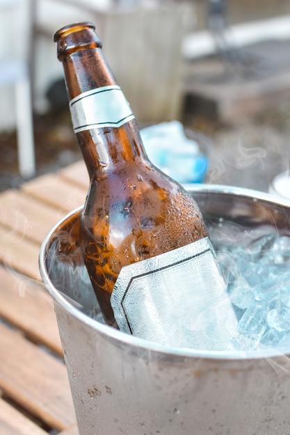 Beer bottle in ice bucket Premium Photo