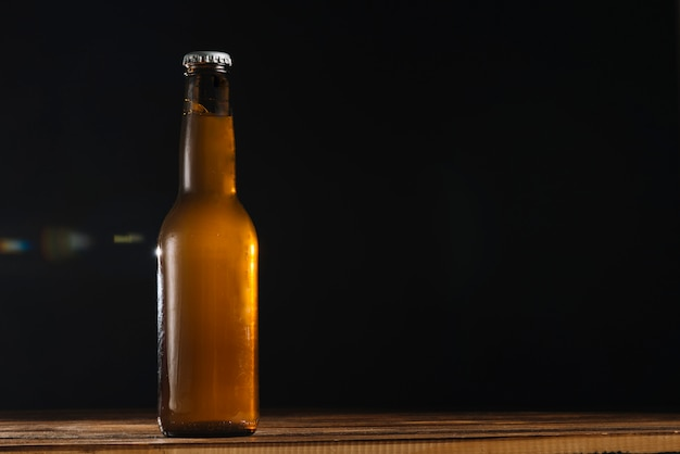 Beer bottle on wooden desk Free Photo