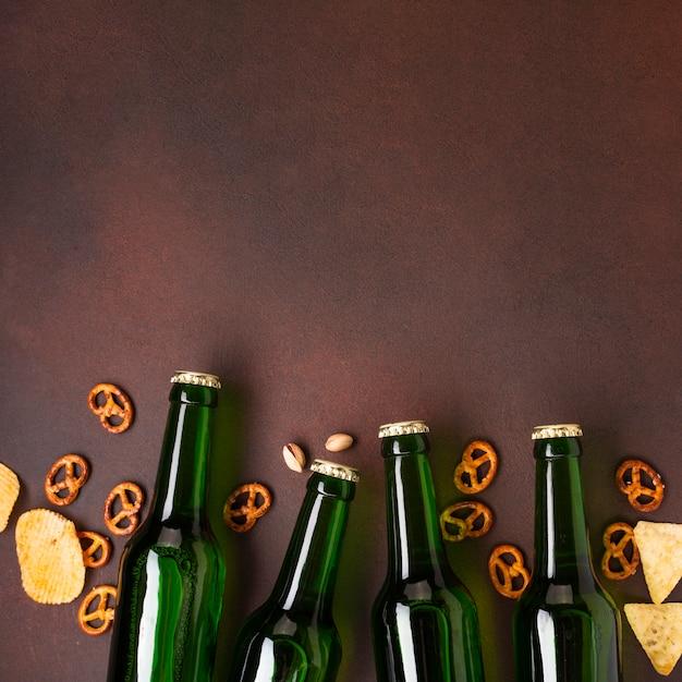 Пивные бутылки и закуски на темном фоне Бесплатные Фотографии