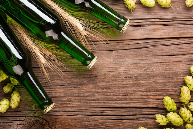 Beer bottles and ingredients of beer on wooden background Free Photo