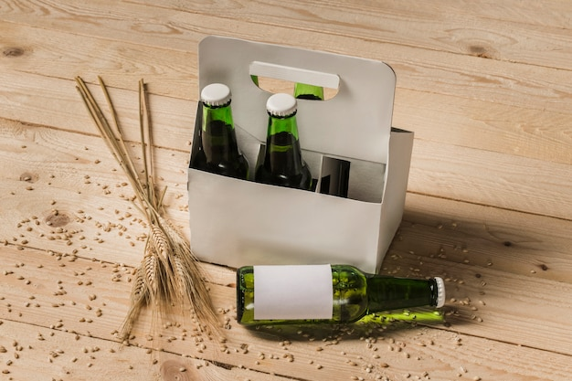 Beer carton box and ears of wheat on wooden background Free Photo