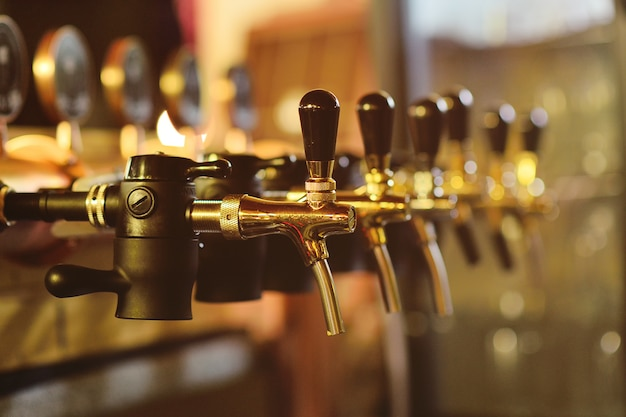 Beer faucet close-up against a bar in the pub Premium Photo