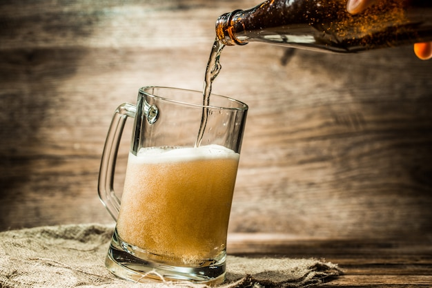 Beer from bottle poured into mug standing on canvas Premium Photo