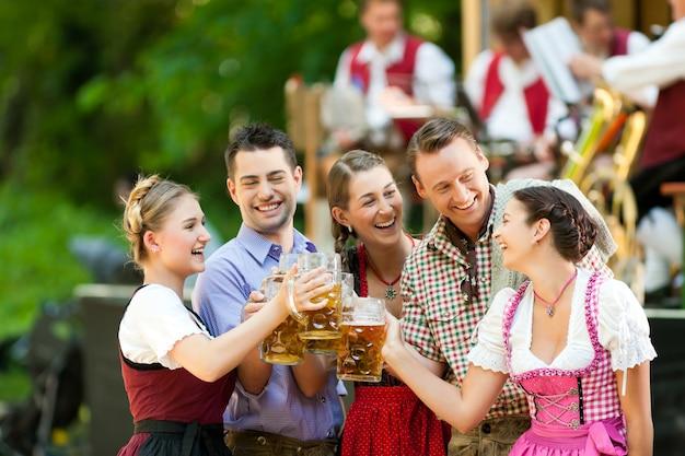 In beer garden - friends in front of band Premium Photo