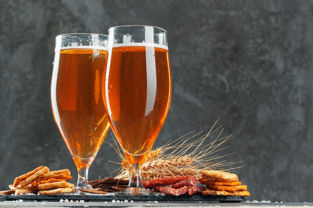 Beer glass with bretzel and dried sausages snacks close up Premium Photo