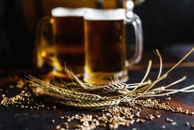 Beer glasses and wheat spice on an old rustic  wood table on black background Premium Photo