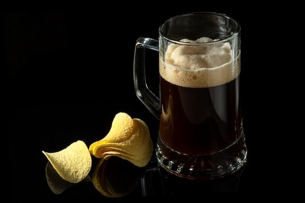 Пиво в прозрачном стакане и картофельные чипсы Premium Фотографии