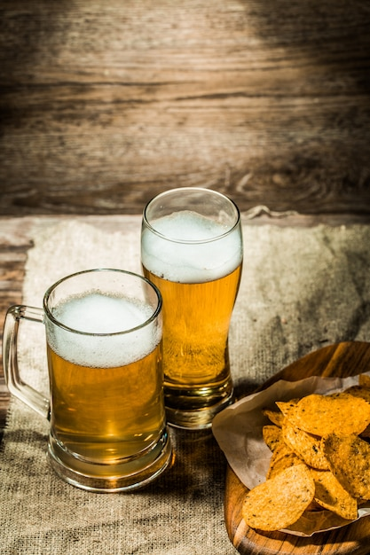Beer in mug, glass on wooden background Premium Photo