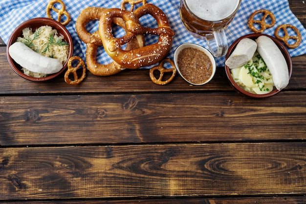 Beer mug, pretzels and sausages on wooden table background in top view Premium Photo