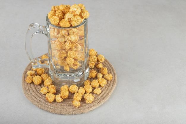 Boccale di birra appoggiato su un sottopentola, riempito di popcorn al caramello, su marmo. Foto Gratuite