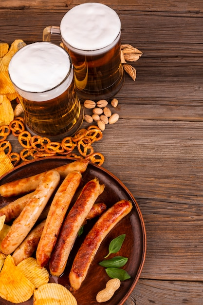 Beer mugs and plate with sausages Free Photo