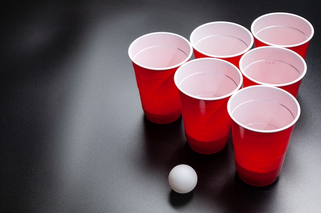 Beer pong college game on black background Premium Photo
