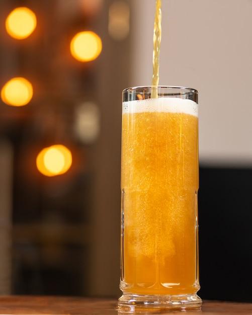 ビールを注ぐ、マグカップに充填、背景のボケ味を持つガラス Premium写真