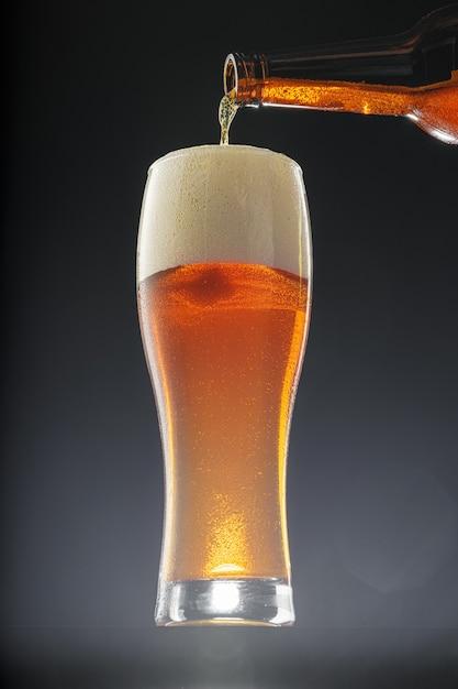 黒の背景にボトルからカップに注ぐビール Premium写真
