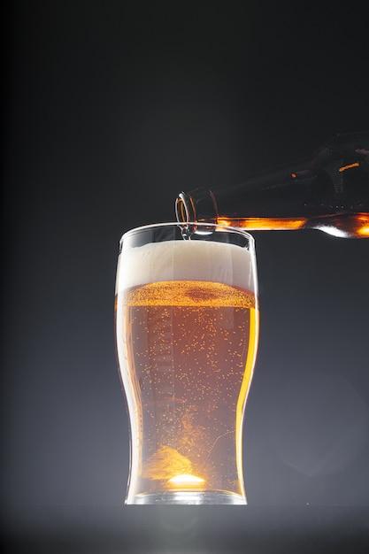 黒の背景にグラスに注ぐビール Premium写真