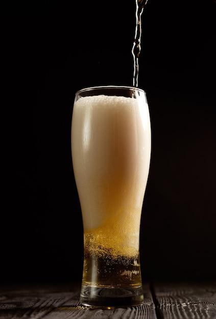 ビールは黒い背景のガラスに注ぐ Premium写真