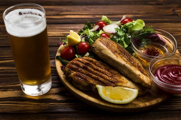 Birra e salsa vicino a pollo e insalata Foto Gratuite