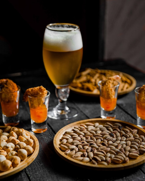 Beer served with beans and dried nuts on the table Free Photo