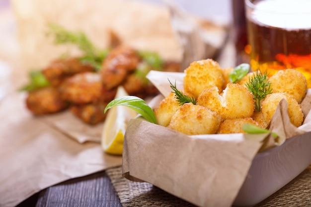 Пивные закуски. жареные жареные рыбные и сырные шарики с лимоном и зеленью. закуски к разному пиву. Premium Фотографии