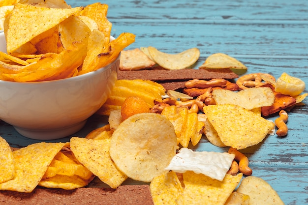Beer snacks like crackers, chips, cookies on a wooden surface Premium Photo