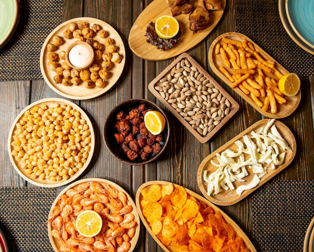 Beer snacks plates of fried dushbara shrimps boiled chickpeas pistachio chips string cheese Free Photo