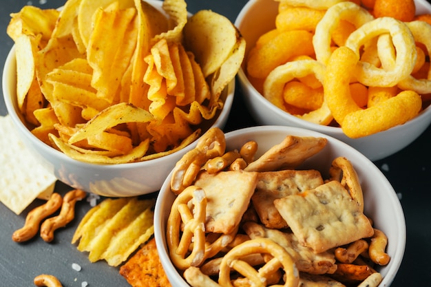 Beer snacks on stone table. various crackers, potato chips. top view Premium Photo