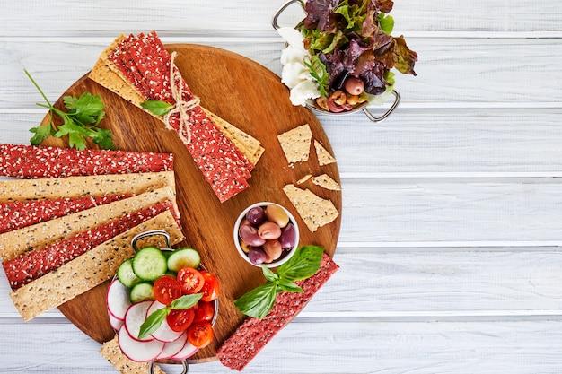 Крекеры из свекольной и ржаной муки с овощами для приготовления закусок на деревянной стене. вегетарианство и здоровое питание Premium Фотографии