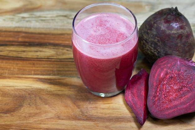 Beetroot juice in clear glass and fresh beetroot on wooden background. Premium Photo