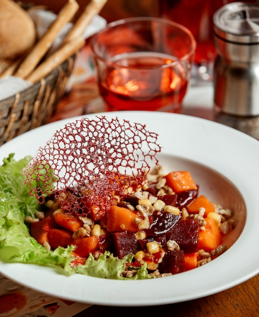 Beetroot salad with carrots, corn and nuts in a white plate Free Photo
