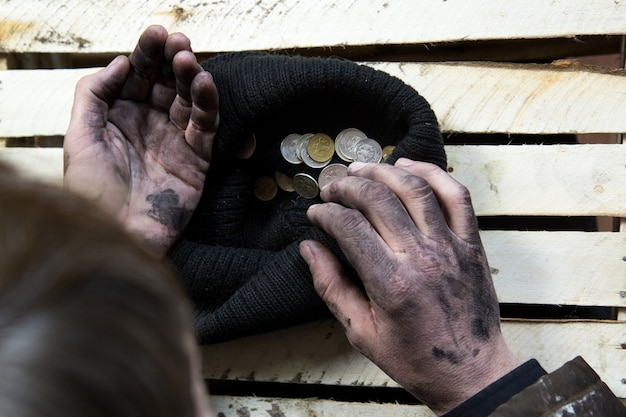 The beggar considers coins. Premium Photo