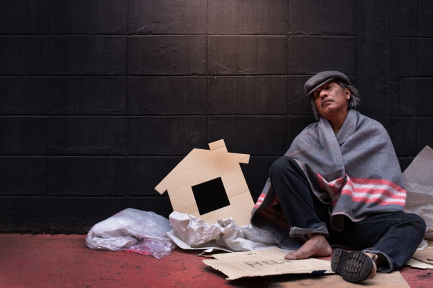 The beggar lean against the wall with fatigue under the blanket Premium Photo