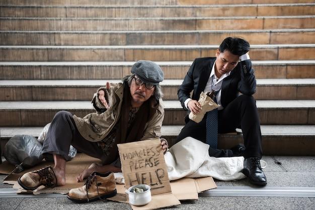 Beggar old man and drunk businessman in town Premium Photo