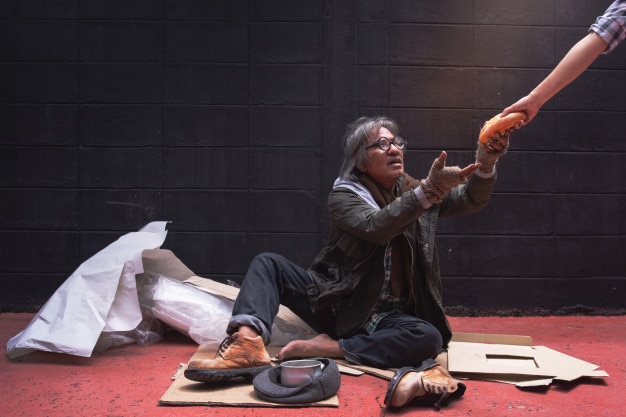 The beggar's hand reaches for bread from a donation Premium Photo
