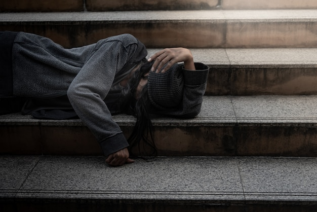 Beggars, homeless people lie on the steps, ask for a fraction of money Premium Photo