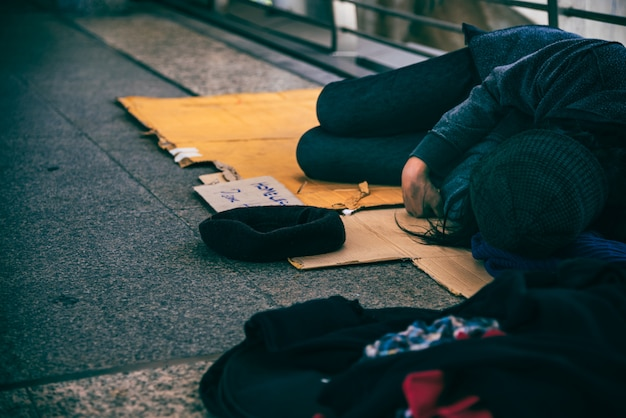 Beggars, homeless people lying on the floor on an overpass. Premium Photo