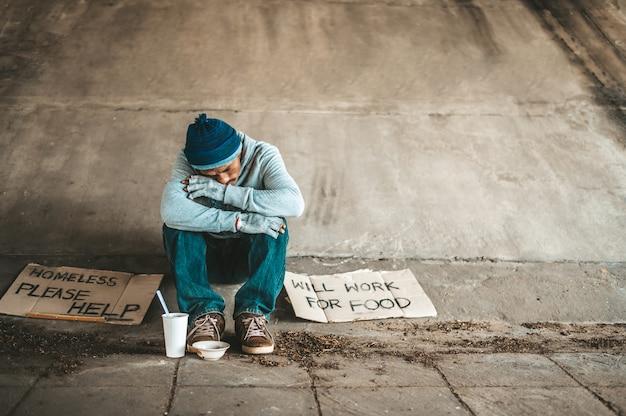 I mendicanti seduti sotto un ponte con le tazze hanno soldi. Foto Gratuite
