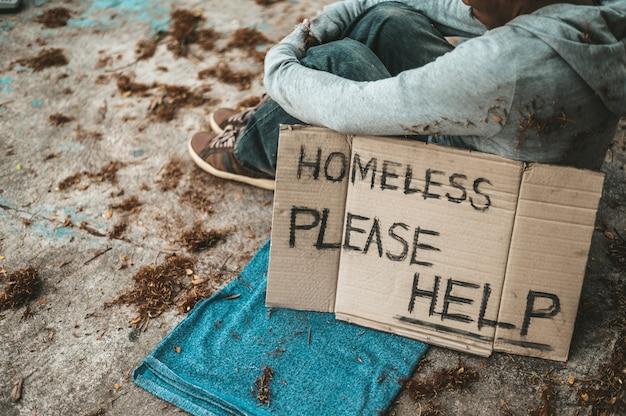 Mendicanti seduti per strada con messaggi per senzatetto, per favore, aiutatemi. Foto Gratuite