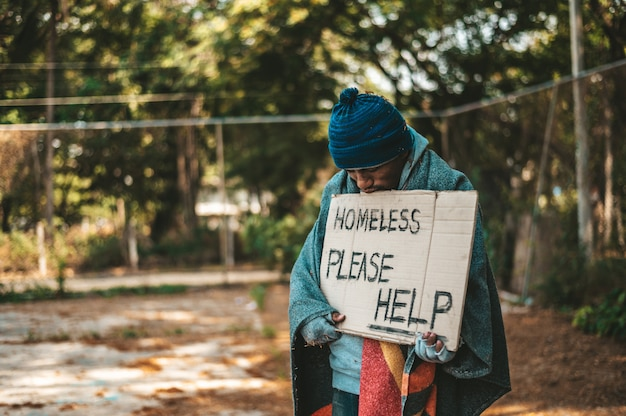 I mendicanti stanno in strada con messaggi di senzatetto per favore aiutatemi. Foto Gratuite
