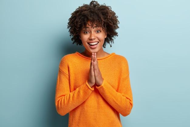 幸せな暗い肌の女性を懇願することは、祈りのジェスチャーで手を保ち、懇願するような表情、前向きな表現を持ち、サポートと助けを求め、オレンジ色のカジュアルジャンパーを着て、青い壁の上のモデル 無料写真