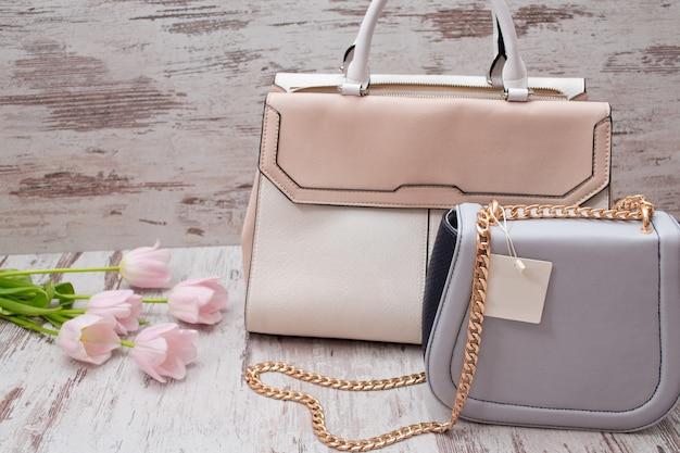 Бежевые и серые сумки на деревянном фоне, розовые тюльпаны. модная концепция. Premium Фотографии